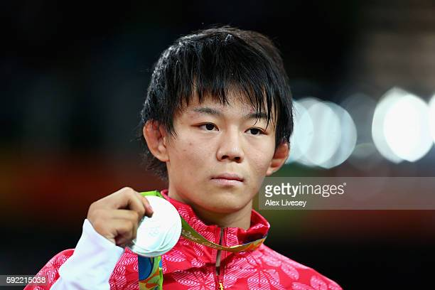Silver medalist Rei Higuchi of Japan celebrates on the podium during the medals ceremony after the Men's 57kg Wrestling match on Day 14 of the Rio...