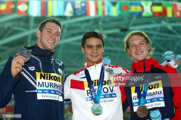 Silver medalist Ryan Murphy of the United States gold medalist Evgeny Rylov of Russia and bronze medalist Luke Greenbank of Great Britain pose during...