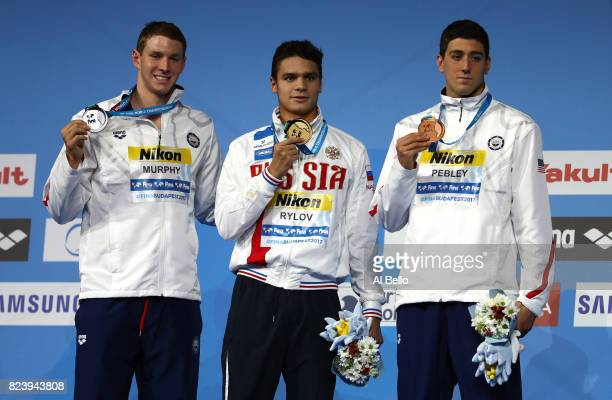 Silver medalist Ryan Murphy of the United States gold medalist Evgeny Rylov of Russia and bronze medalist Jacob Pebley of the United States pose with...