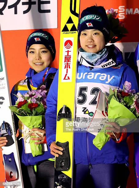 Silver medalist Sara Takanashi and gold medalist Yuki Ito celebrate on the podium at the medal ceremony for the HS 106 Normal Hill during day two of...