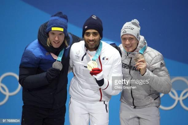 Silver medalist Sebastian Samuelsson of Sweden, gold medalist Martin Fourcade of France and bronze medalist Benedikt Doll of Germany celebrate during...