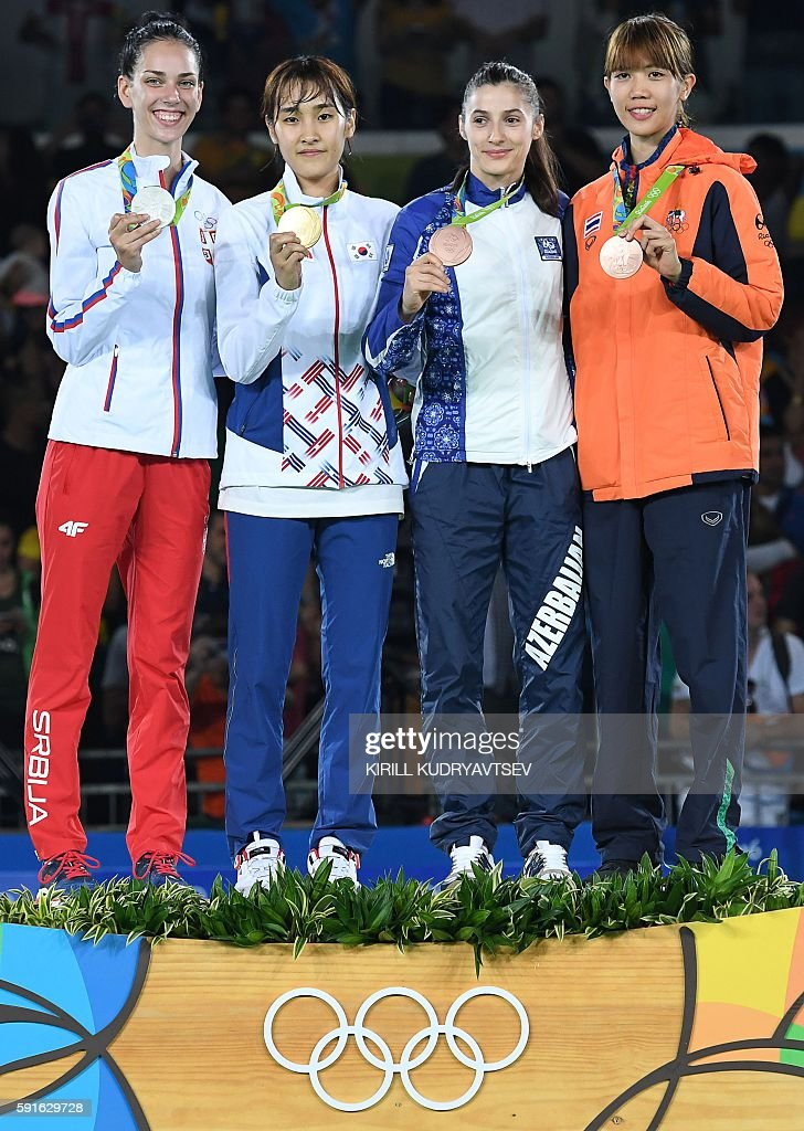 Silver medalist Serbia's Tijana Bogdanovic, gold medalist South Korea's Kim Sohui, and bronze medalists Azerbaijan's Patimat Abakarova and Thailand's Panipak Wongpattanakit pose with their medals on the podium after the womens taekwondo event in the -49kg category as part of the Rio 2016 Olympic Games, on August 17, 2016, at the Carioca Arena 3, in Rio de Janeiro. / AFP / Kirill KUDRYAVTSEV