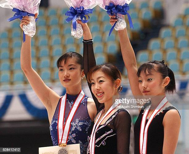 Silver medalist Shizuka Arakawa gold medalist Fumie Suguri and bronze medalist Miki Ando celebrate on the podium at the medal ceremony for the...