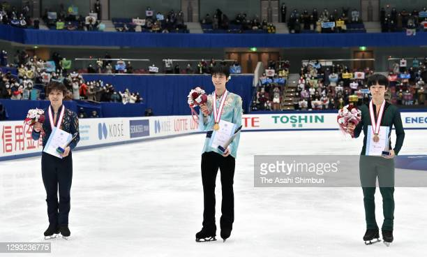 Silver medalist Shoma Uno, gold medalist Yuzuru Hanyu and bronze medalist Yuma Kagiyama pose at the medal ceremony for the Men's Single on day two of...
