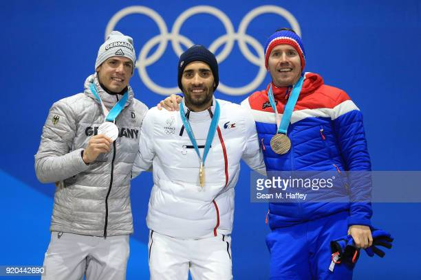 Silver medalist Simon Schempp of Germany, gold medalist Martin Fourcade of France and bronze medalist Emil Hegle Svendsen of Norway celebrate during...