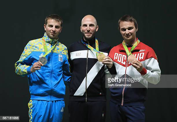 Silver medalist Sirhiy Kulish of the Ukraine gold medalist Niccolo Campriani of Italy and Vladimir Maslennikov of Russia pose on the podium during...