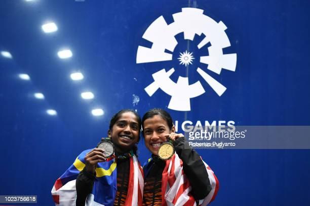 Silver medalist Sivasangari Subramaniam of Malaysia and gold medalist Nicol Ann David of Malaysia celebrate on the podium during Women's Squash...