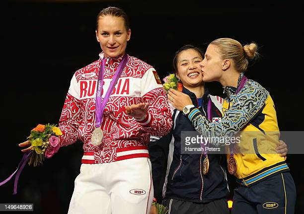 Silver medalist Sofya Velikaya of Russia gold medalist Jiyeon Kim of Korea and bronze medalist Olga Kharlan of Ukraine pose on the podium during the...