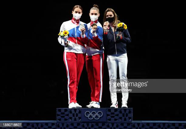 Silver medalist Sofya Velikaya of Team ROC, gold medalist Sofia Pozdniakova of Team ROC, and bronze medalist Manon Brunet of Team France, pose on the...