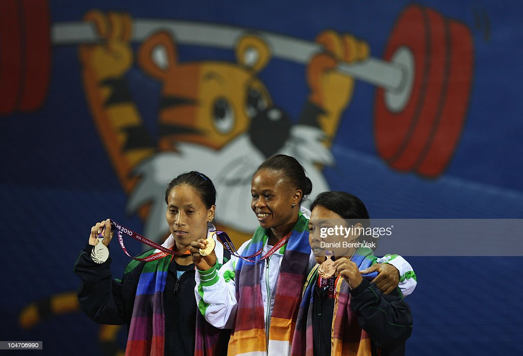 Silver medalist Soniya Chanu Ngangbam of India, gold medalist Augustina Nkem Nwaokolo of Nigeria and bronze medalist Sandhya Rani Devi Atom of India pose on the podium during the presentation for the Women�s 48kg weightlifting during day one of the Delhi 2010 Commonwealth Games at Jawaharlal Nehru Sports Complex on October 4, 2010 in Delhi, India.