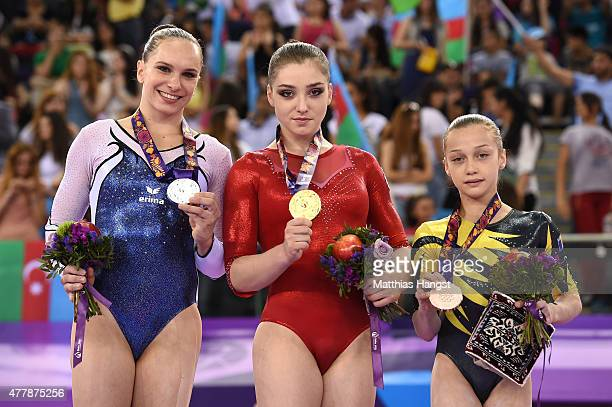Silver medalist Sophie Scheder of Germany gold medalist Aliya Mustafina of Russia and bronze medalist Andreea Iridon of Romania stand on the podium...