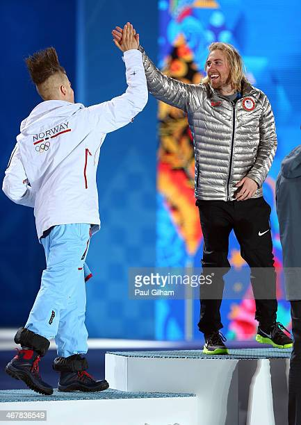 Silver medalist Staale Sandbech of Norway high fives gold medalist Sage Kotsenburg of the United States on the podium during the medal ceremony for...