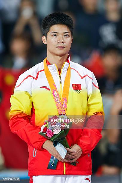 Silver medalist Su Bingtian of China poses for photographs during the victory ceremony for theMen's 100m Final during day nine of the 2014 Asian...