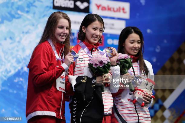 Silver medalist Sydney Pickrem of Canada gold medalist Yui Ohashi of Japan and bronze medalist Miho Teramura of Japan celebrate on the podium at the...