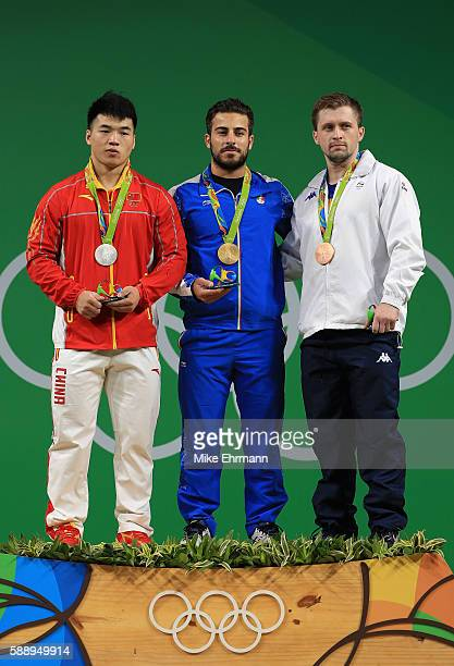 Silver medalist Tao Tian of China gold medalist Rostami Kianoush of Iran and bronze medalist Gabriel Sincraian of Roumania stand on the podium during...
