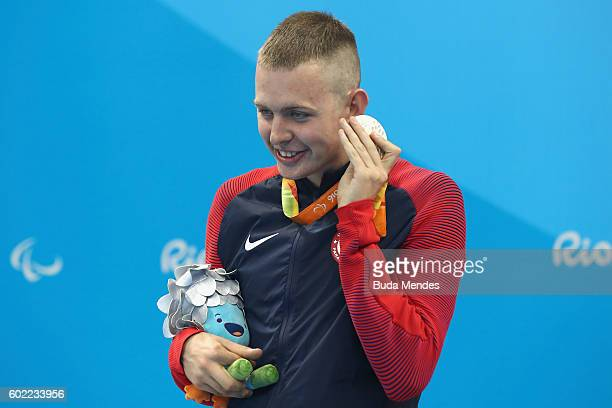 Silver medalist Tharon Drake of the United States listens to the sound of his medal on the podium at the medal ceremony for the Men's 400m Freestyle...
