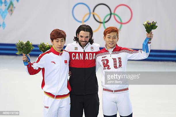 Silver medalist Tianyu Han of China gold medalist Charles Hamelin of Canada and bronze medalist Victor An of Russia celebrate on the podium during...