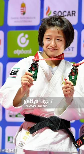 Silver medalist Tsukasa Yoshida of Japan poses for photographs on the podium at the medal ceremony for the Women's 57kg during day three of the World...