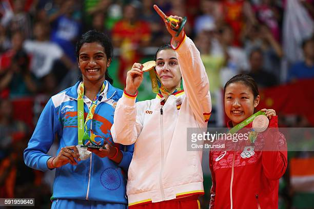 Silver medalist V Sindhu Pusarla of India gold medalist Carolina Marin of Spain and bronze medalist Nozomi Okuhara of Japan celebrate during the...