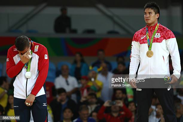 Silver medalist Varlam Liparteliani of Georgia and gold medalist Mashu Baker of Japan stand on the podium during the medal ceremony for the Men's...