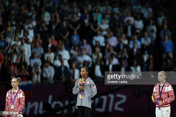 Silver medalist Victoria Komova of Russia gold medalist Gabrielle Douglas of the United States and bronze medalist Aliya Mustafina of Russia pose...