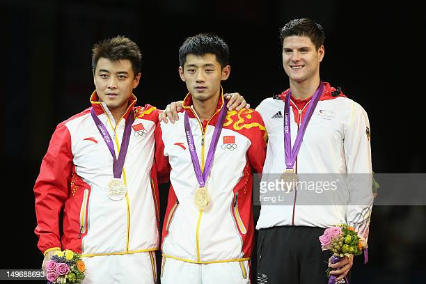 Silver medalist Wang Hao of China, gold medalist Zhang Jike of China and bronze medalist Dimitrij Ovtcharov of Germany pose on the podium during the...
