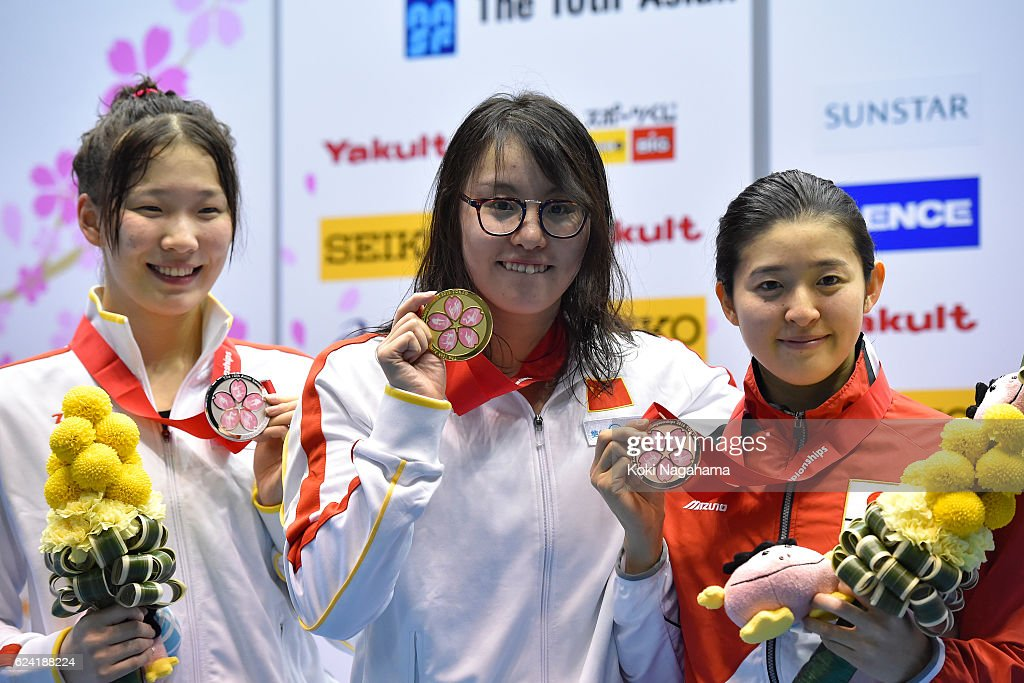 Silver medalist Wang Xueer of China and Gold medalist Fu Yuanhui of China and BronzE medalist Emi Moronuki of Japan pose for photographs after Women's 100m Backstroke final race during the 10th Asian Swimming Championships 2016 at the Tokyo Tatsumi International Swimming Center on November 18, 2016 in Tokyo, Japan.