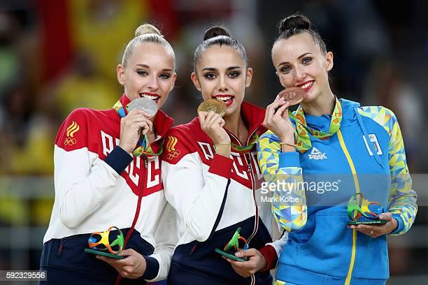 R] Silver medalist Yana Kudryavtseva of Russia gold medalist Margarita Mamun of Russia and bronze medalist Ganna Rizatdinova of Ukraine celebrate on...