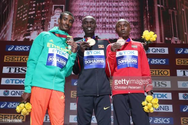 Silver medalist Yomif Kejelcha of Ethiopia, gold medalist Joshua Cheptegei of Uganda and bronze medalist Rhonex Kipruto of Kenya stand on the podium...