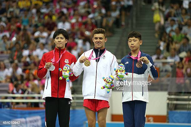 Silver medalist Yuasa Kenya of Japan Gold medalist Giarnni ReginiMoran of Great Britain and Bronze medalist Lim Myongwoo of South Korea celebrate...