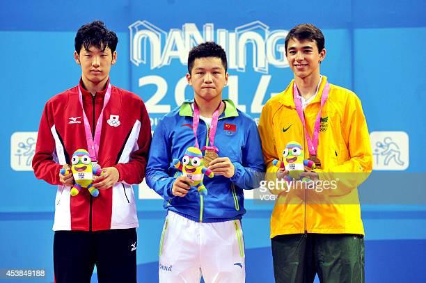 Silver medalist Yuto Muramatsu of Japan Gold medalist Fan Zhendong of China and Bronze medalist Hugo Calderano of Brazil celebrate on the podium...