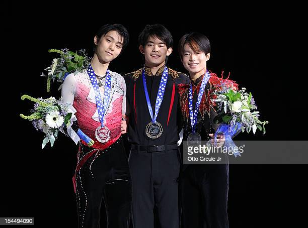 Silver medalist Yuzuru Hanyu gold medalist Takahiko Kozuka and bronze medalist Tatsuki Machida of Japan pose for photos after the men's free skate...