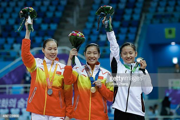 Silver medalist Zhong Xingping Gold medalist Li Dan of China and Bronze medalists Ayano Kishi of Japan celebrates during the medal ceremony after the...