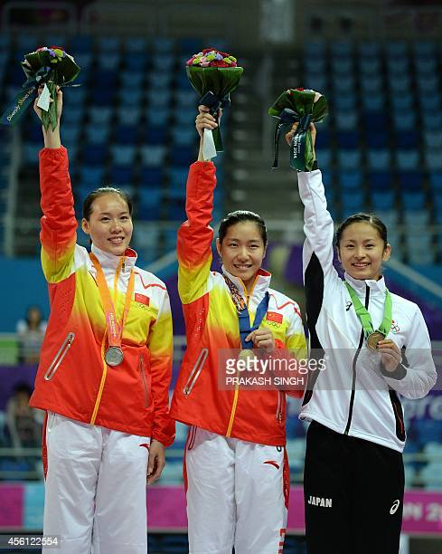 Silver medalist Zhong Xingping of China gold medalist Li Dan of China and bronze medalist Ayano Kishi of Japan pose during the medal ceremony for the...
