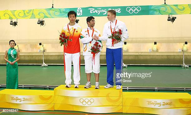 Silver medalist Zhu Qinan of China Gold medalist Abhinav Bindra of India and Bronze medalist Henri Hakkinen of Finland celebrate on the podium after...
