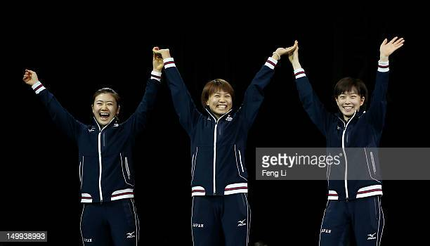 Silver medalists Ai Fukuhara Sayaka Hirano and Kasumi Ishikawa of Japan celebrate on the podium during the medal ceremony for the Women's Team Table...