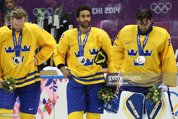 Silver medalists Alexander Edler Johnny Oduya and Henrik Lundqvist of Sweden react during the medal ceremony after losing to Canada 30 during the...