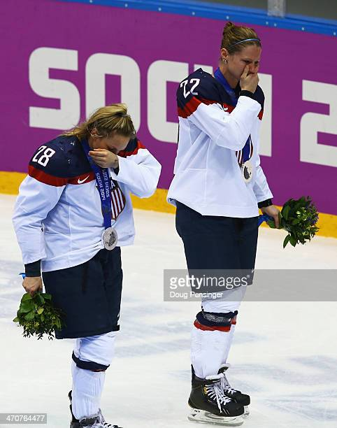 Silver medalists Amanda Kessel and Kacey Bellamy of the United States react during the flower ceremony after losing 32 to Canada in overtime during...