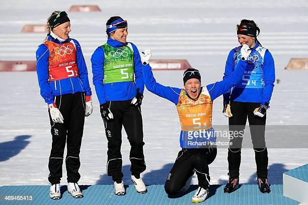 Silver medalists Anne Kylloenen AinoKaisa Saarinen Kerttu Niskanen and Krista Lahteenmaki of Finland celebrate on the podium during the flower...