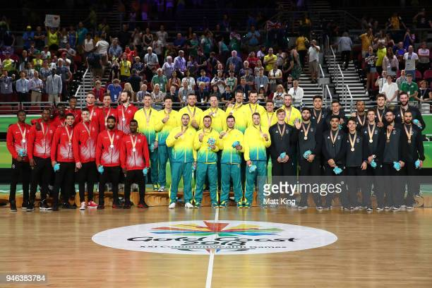 Silver medalists Canada, gold medalists Australia and bronze medalists New Zealand pose during the medal ceremony for the Men's Basketball on day 11...
