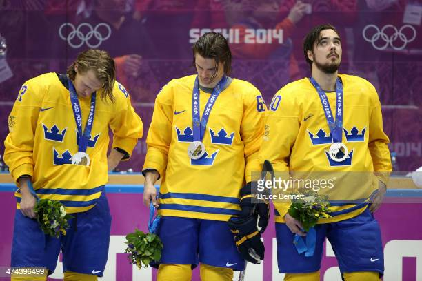Silver medalists Carl Hagelin Erik Karlsson and Marcus Johansson of Sweden react during the medal ceremony after losing to Canada 30 during the Men's...