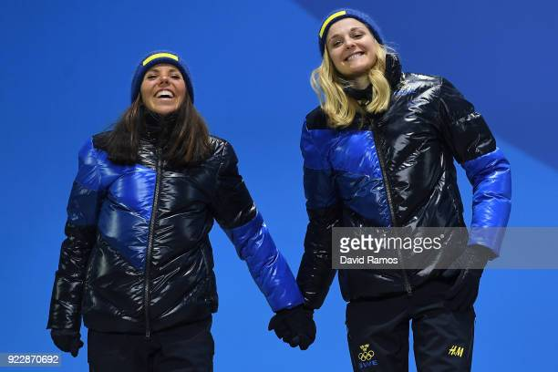 Silver medalists Charlotte Kalla and Stina Nilsson of Sweden celebrate during the medal ceremony for CrossCountry Skiing Ladies' Team Sprint Free on...