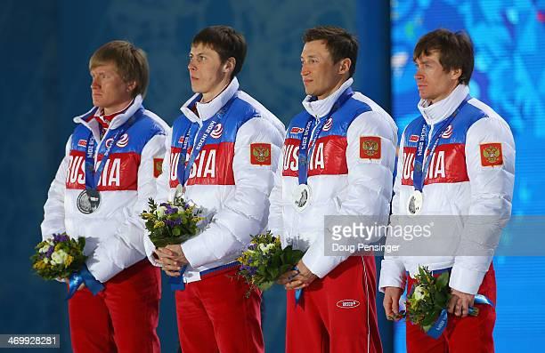 Silver medalists Dmitriy Japarov Alexander Bessmertnykh Alexander Legkov and Maxim Vylegzhanin of Russia celebrate on the podium during the medal...
