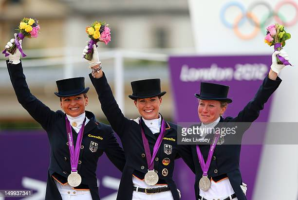 Silver medalists Dorothee Schneider Kristina Sprehe and Helen Langehanenberg of Germany celebrate with their medals during the medal cerermony for...