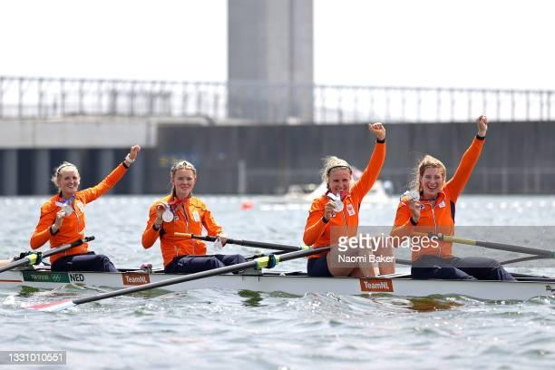 Silver medalists Ellen Hogerwerf, Karolien Florijn, Ymkje Clevering and Veronique Meester of Team Netherlands pose with their medals on their boat...