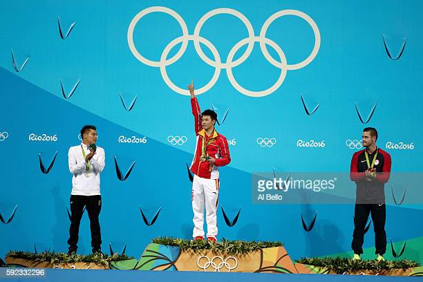 Silver medalists German Sanchez of Mexico gold medalist Aisen Chen of China and bronze medalists David Boudia of the United States pose on the podium...