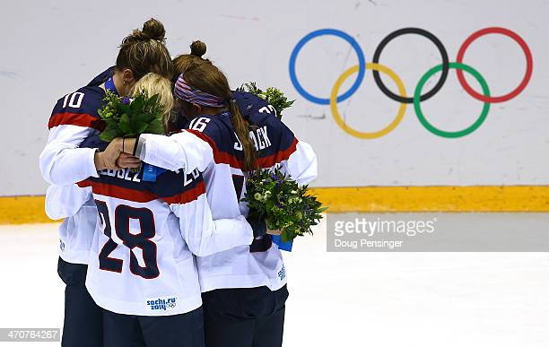 Silver medalists Kelli Stack Meghan Duggan Amanda Kessel and Kacey Bellamy of the United States react during the flower ceremony after losing 32 to...