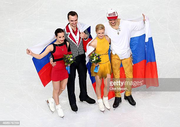 Silver medalists Ksenia Stolbova and Fedor Klimov of Russia gold medalists Tatiana Volosozhar and Maxim Trankov of Russia pose after the flower...