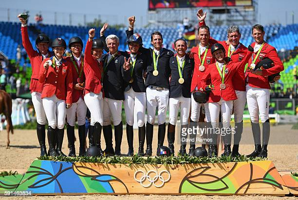 Silver medalists Lucy Davis of United States riding Barron, Kent Farrington of the United States riding Voyeur, McLain Ward of United States riding...
