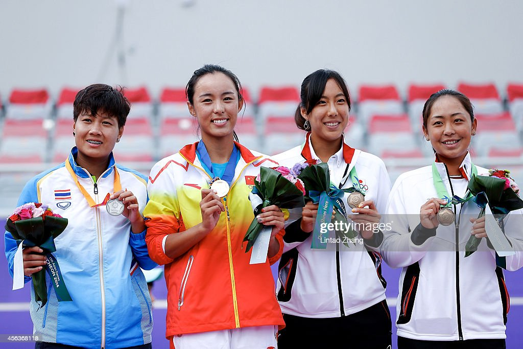 Silver medalists Luksika Kumkhum of Thailand, gold medalists Wang Qiang of China and bronze medalists Eri Hozumi and Misa Eguchi of Japan celebrate during the medal ceremony after the Tennis Women's Singles Gold Medal Match on day eleven of the 2014 Asian Games at Yeorumul Tennis Courts on September 30, 2014 in Incheon, South Korea.